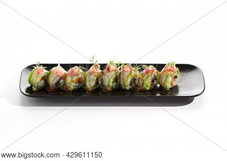 Avocado sushi with salmon, cream cheese and mango on white background. Sushi roll avocado outside, topped with spicy sauce and fresh greens. Sushi food menu restaurant. Sushi roll on black plate