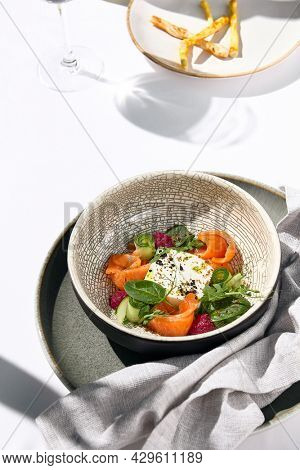 Homemade cheese salad with salmon, cucumber and beetroot. Fancy dinning with salmon salad on white table with simple contemporary decoration. Sunlight and harsh shadow still life. Salmon salad bowl