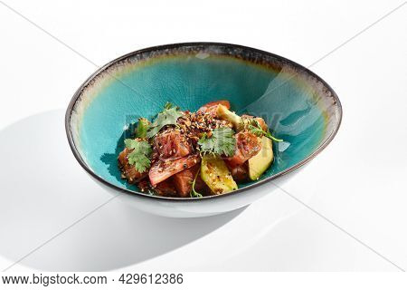 Salmon and avocado salad bowl. Blue salad bowl isolated on white background. Salad garnished with micro greens and sesame, chopped salmon, sliced avocado and parsley green leaf