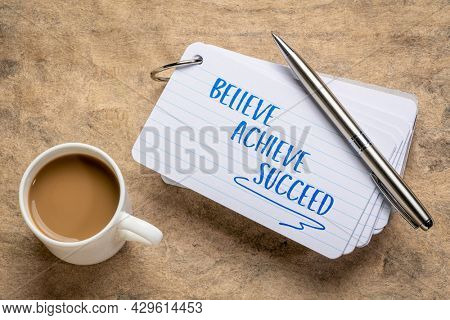 believe, achieve, succeed motivational words - handwriting on a stuck of index card with a cup of coffee, business, goal setting and personal development concept