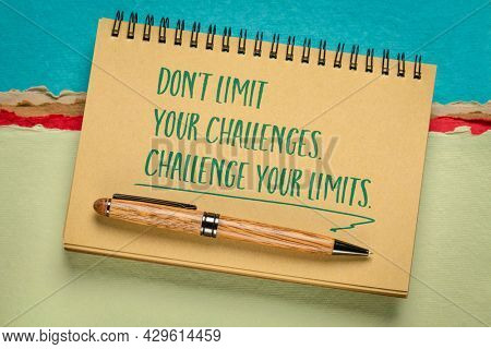 do not limit your challenges, challenge your limits - inspirational reminder, handwriting in a spiral notebook against abstract paper landscape, mindset and personal development concept