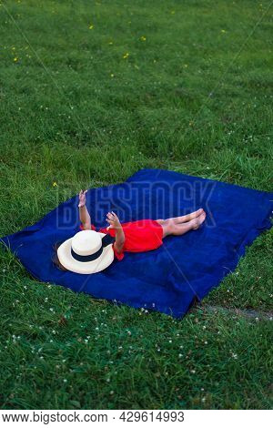Girl In A Hat And In A Red Dress Sunbathes On The Green Grass. No Face