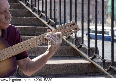An Adult Elderly Man Of Retirement Age Plays An Old Six-string Classical Acoustic Guitar Outdoors Wh