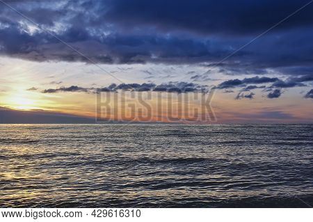 Sunset Over The Sea. There Are Dark Blue Clouds Over The Water. Small Waves And Ripples On The Surfa