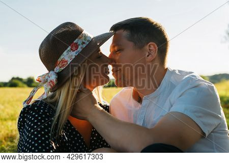 Happy Young Couple Kissing At Sunset Outdoors, Man Gently Caresses His Girlfriend In Straw Hat. Port