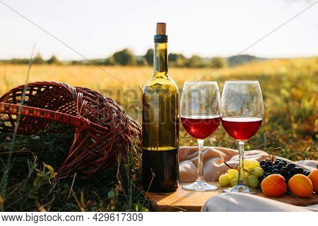 Picnic, Romantic Evening In Nature Concept. Bottle Of Red Wine, Glasses With Drink, Grapes, Peaches
