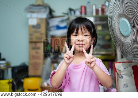 Cute Asian Child Girl Sweet Smile. Happy Kid Raise Finger In A V Shape, Raise Her Index And Middle F
