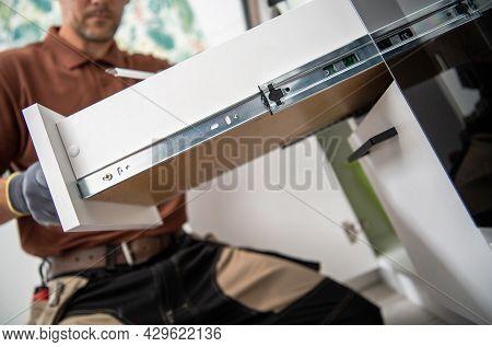 Modern Kitchen Cabinet Drawer Installation By Caucasian Professional Cabinetmaker Technician.