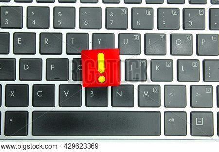 A Red Cube With A Yellow Exclamation Mark And A Laptop Background. The Concept Of Exclamation Marks.