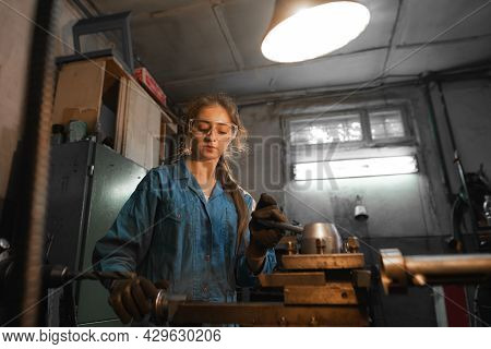 Young Woman In Her Garage Works On A Lathe. Profession Concept Turner, Metalworking, Turning, Indust