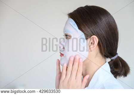 Portrait Of Young Woman Applying Facial Mask For Enhance Her Skin, Side View. Facial Mask Is A Cream