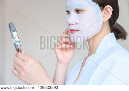 Portrait Of Young Woman Looking Her Face In Mirror After Applying Facial Mask For Enhance Her Skin.