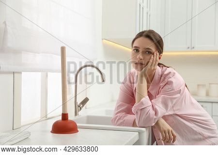 Unhappy Young Woman With Plunger Near Clogged Sink In Kitchen
