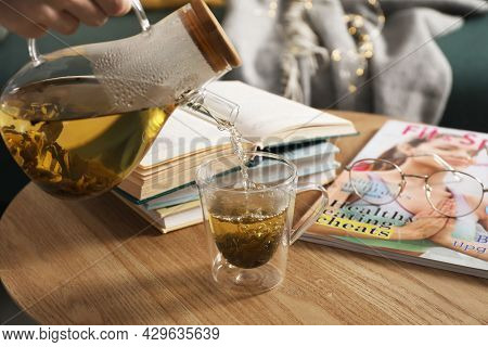 Woman Pouring Freshly Brewed Tea Into Cup At Table In Living Room, Closeup. Cozy Home Atmosphere