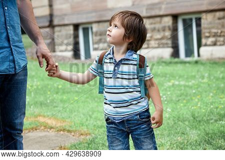 Dad Is Holding His Sons Hand. Back To School. The Boy Goes To The Kindergarten. Care Of Parents, Par