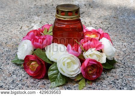 A Grave Candle And A Rose Arrangement On A Gravestone