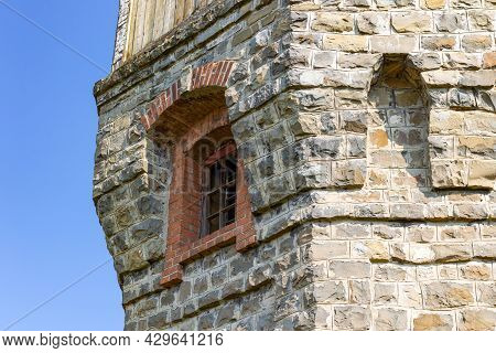 The Upper Part Of An Ancient Watchtower Made Of Stone Blocks And Wood Paneling With Windows Against