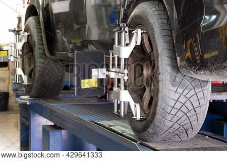 Car Tire Clamped With Aligner Undergoing Auto Wheel Angle Adjustment, Alignment And Wheel Balance In