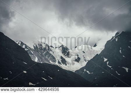 Dark Atmospheric Mountain Landscape With Glacier On Black Rocks In Lead Gray Cloudy Sky. Snowy Mount