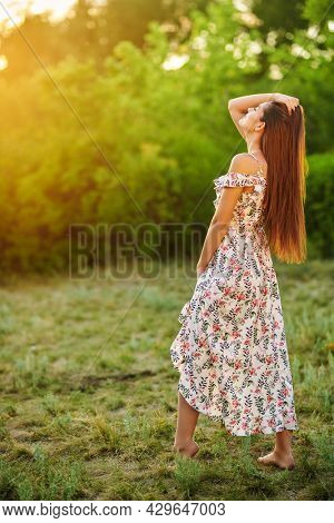 Full length portrait of lovely young girl posing in a summer floral dress barefoot on lawn outdoor in sunny day. Summer fashion and beauty.