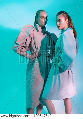 Fashion models girls pose in stylish clothes from the spring-summer collection. Full length studio portrait in aquamarine light. Haute couture clothing.