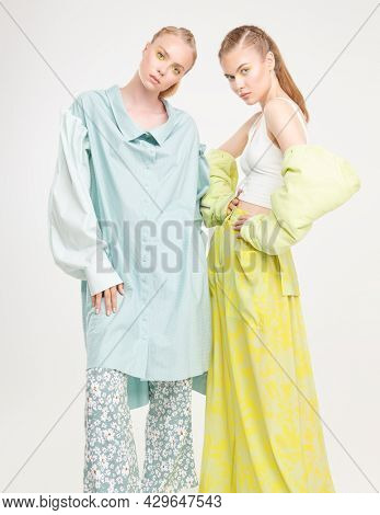 Two beautiful fashion models girls pose in elegant summer clothes and clogs. Romantic summer style. Full length studio portrait on a white background. Fashion.
