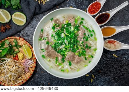 Soup Pho Bo With Beef, Lime And Spices On Black Stone Table With Sauces, Vietnamese Food Top View