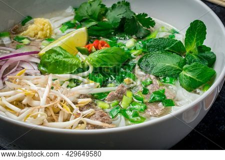 Soup Pho Bo With Beef, Lime And Spices On Black Stone Table With Sauces, Vietnamese Food Close Up