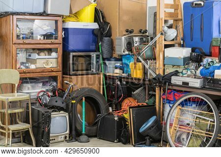 Hoarder clutter and household junk crowding the corner of a messy suburban garage.