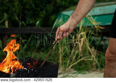 A Man Holds A Stick In His Hands And Kindles Fire In Nature.concept Of Outdoors Picnic.
