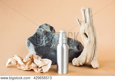 Metallic Cosmetic Container On Background Of A Stone And A Wooden Branch. Concept Of Environmentally
