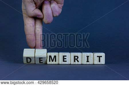 Demerit Or Merit Symbol. Businessman Turns Wooden Cubes And Changes Words 'demerit' To 'merit'. Beau