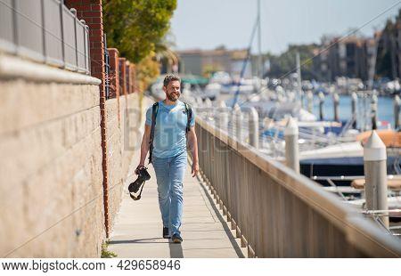 Vacation Photographer. Travel Photographer Promenade Holding Camera. Summer Traveller Go Sightseeing