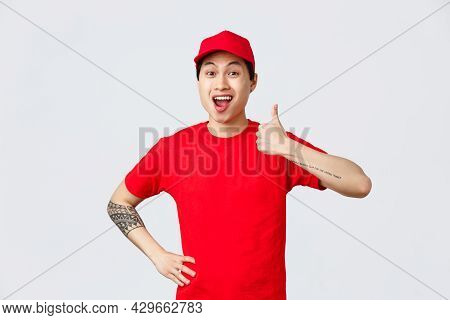 Very Good Delivery Company. Cheerful Asian Courier In Uniform, Red Cap And T-shirt, Encourage Shop S