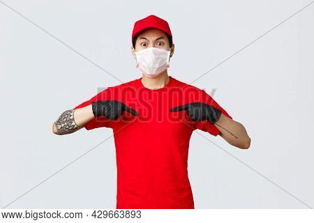 Shocked And Questioned Asian Delivery Man In Uniform Red Cap And T-shirt, Wearing Protective Medical