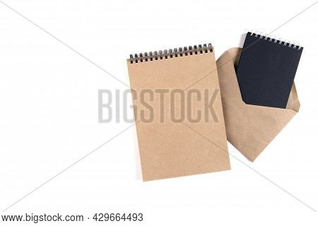 Blank Spiral Notepads And A Recycled Envelope Stacked On A White Background. Education, Office, Envi