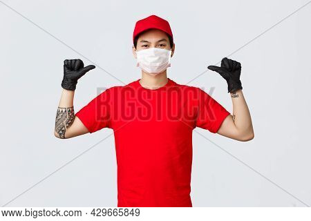 Confident Delivery Guy Pointing Himself, Out Company Can Do It. Enthusiastic Courier In Red Uniform,