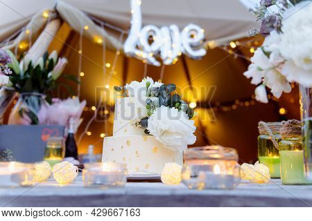 Two Tiered Wedding Cake Decorated With Fresh Peony Flowers And Edible Gold On The Wooden Table With