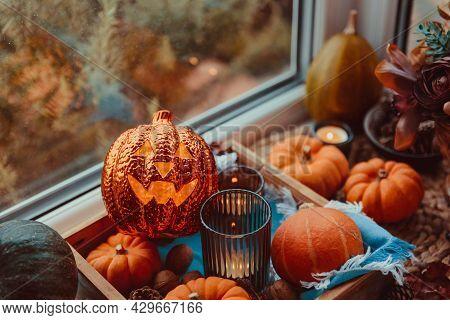 Halloween Cozy Mood Composition On The Windowsill. Lighting Jack-o-lantern, Decorative Pumpkins, Con