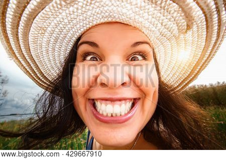 Portrait Of A Woman In A Hat Close-up, Full-face, On A Wide-angle Lens. Distorted Proportions, Funny