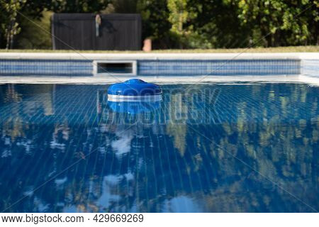 A Pool Chlorine Dispenser Floating In The Clear Water Of The Pool. You Can See The Crystal Clear Wat