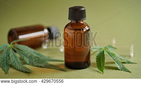 Medical Marijuana Cannabis Oil Extract In Bottle Green Hemp Leaves And Glass Test Tubes On A Green B