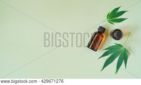 Medical Marijuana Cannabis Oil Extract In Bottle Green Hemp Leaves And Glass Test Tubes Green Backgr