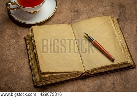 blank antique leather-bound journal with decked edge handmade paper pages with a stylish pen and cup of tea against handmade paper, journaling concept