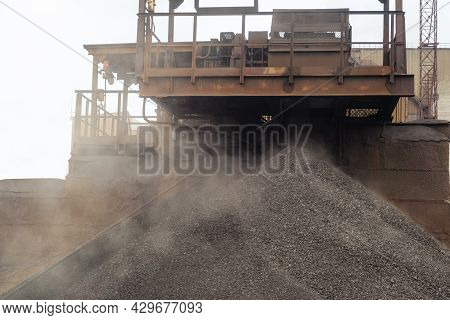 Iron Ore Pellets Are Piled From The Conveyor Belt Into A Heap. Falling Of Spherical Lumps Of Crushed
