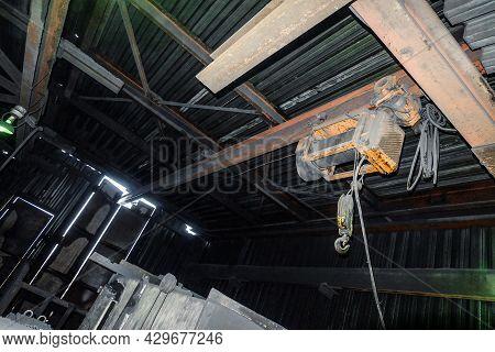 Overhead Traveling Cathead With Steel Hook On Monorail In Industrial Room. Steel Slings.