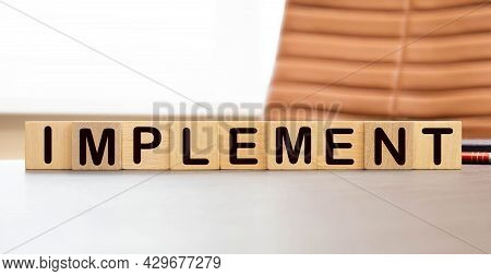 Text Implement On Wood Cube Block, Stock Investment Concept. The Text Implement Is Written On The Cu