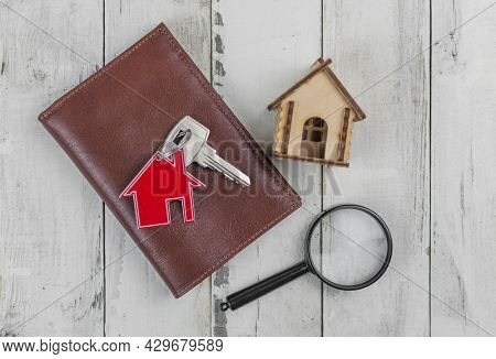 Metal keyring in the shape of a house with a metal key and magnifying glass on a white wood plank background. Real estate concept