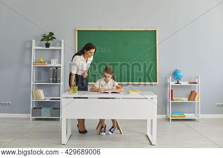 Friendly School Teacher Helping Little Pupil With Math Assignment In Modern Classroom