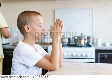 Caucasian Boy Prays At Home At The Table Before Eating. Stay Home And Pray To God. Online Church Ser